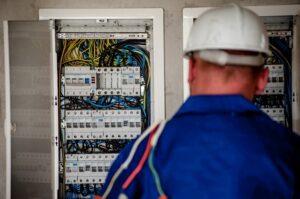 An electrician facing an electric switchboard