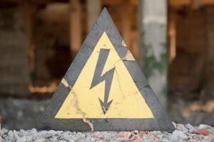 A damaged triangular caution high voltage warning sign