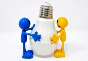 Two cartoon figures (blue and yellow) holding an LED light bulb