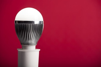 An LED bulb on a holder in front of a red background