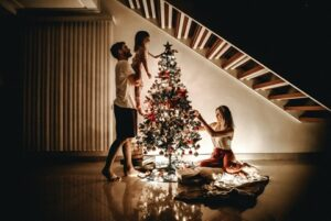 a family decorating a Christmas tree safely