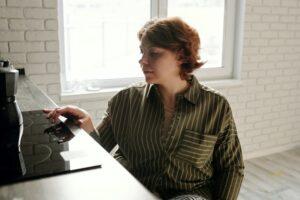 Woman checking malfunctioning electric cooking range