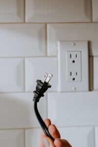 person holding a black two pin plug