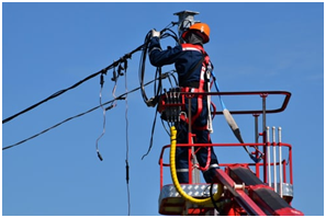 A man in red and black jacket wearing an orange helmet fixing an electrical wire